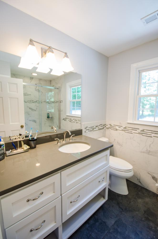 Beautiful bathroom vanity with undermount sink, new bathroom fixtures, and stone wall surround.