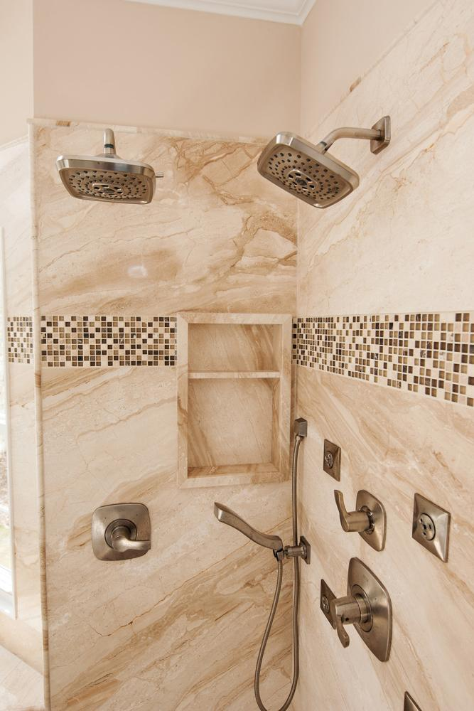 Real natural stone shower with tile mosaic, shelving, and double shower heads.