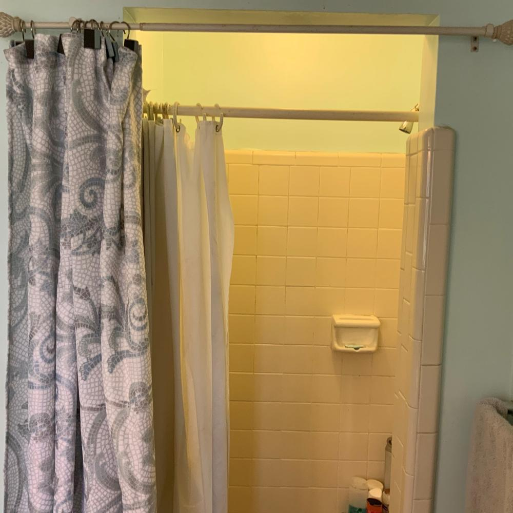 The shower looks dark, small and outdated