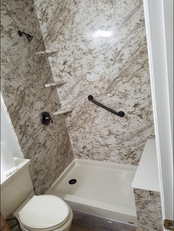 Custom Shower featuring low threshold shower pan, seating, and grab bars